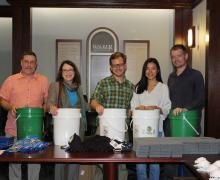 Walker College of Business Dean Norris, second from left, with AppState Executive Impact Club members Tim Walker, Logan Edwards, Teea Wan and Wade Hampton assemble flood buckets for hurricane relief.