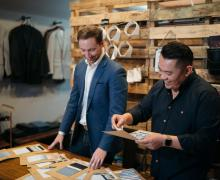 Appalachian alumni Bradley Rhyne '07, left, and Filipe Ho '07 review fabric swatches at their OLE MASON JAR menswear shop in Charlotte. Photo submitted
