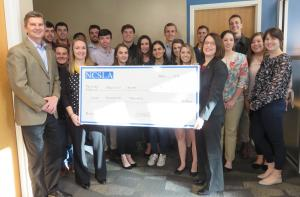 NCSLA Stamping Office Chair Danielle Wade, holding check at left, with Brantley Risk & Insurance Center Director Dave Marlett, far left, Walker College of Business Dean Heather Norris, holding check at right, and student participants of the 2018 London trip