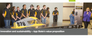 Chancellor Sheri N. Everts admires Appalachian State University's solar vehicle, Apperion, and its 2017 display of sponsors at an unveiling in early April. Some members of Team Sunergy look on. Photo by Marie Freeman