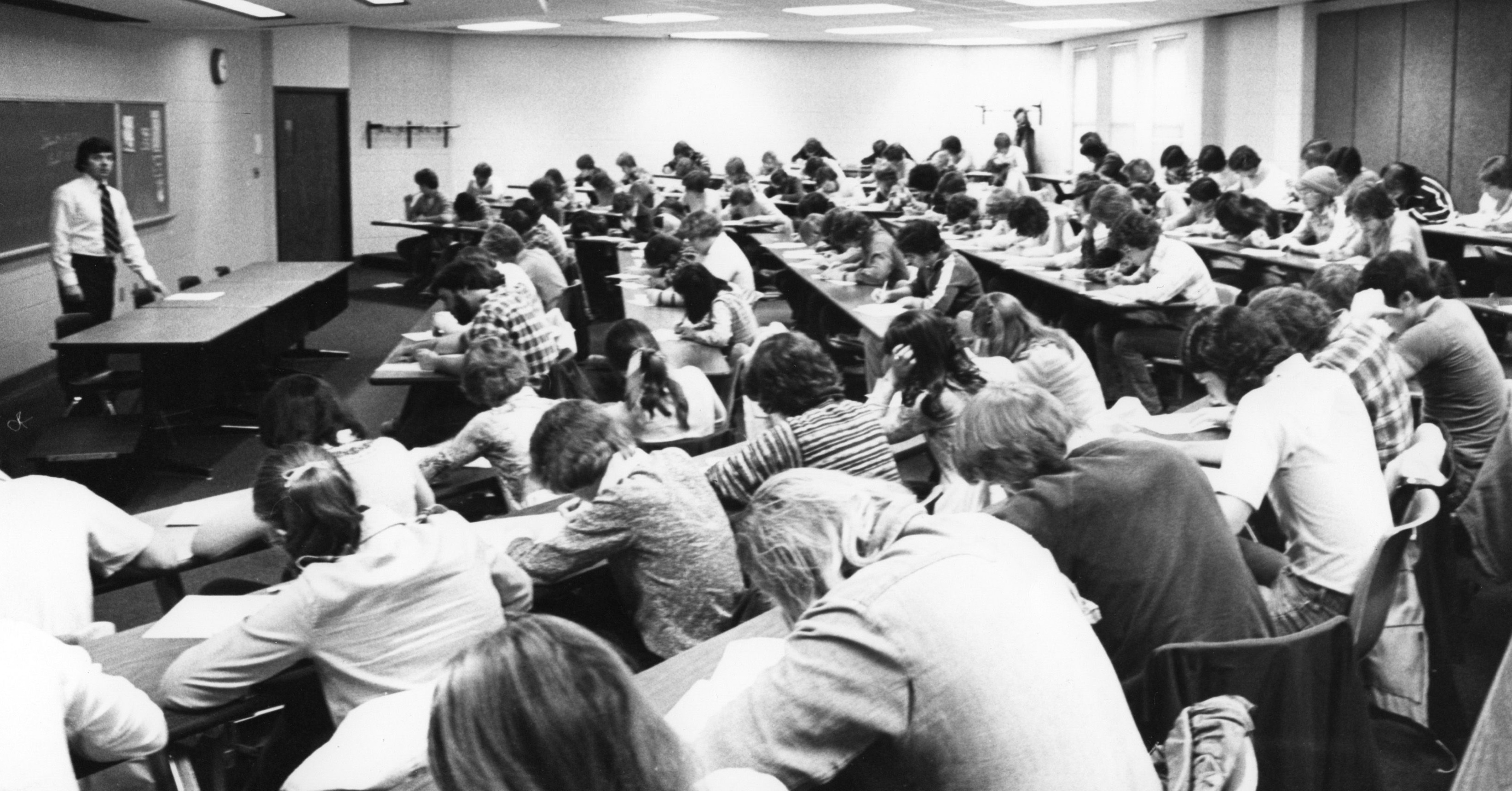 This image shows a class taught in the College of Business at Appalachian State University (1967-current) in the 1970s. A professor can be seen standing behind a desk on the left and students can be seen sitting at desks, writing, on the right. The Colleg