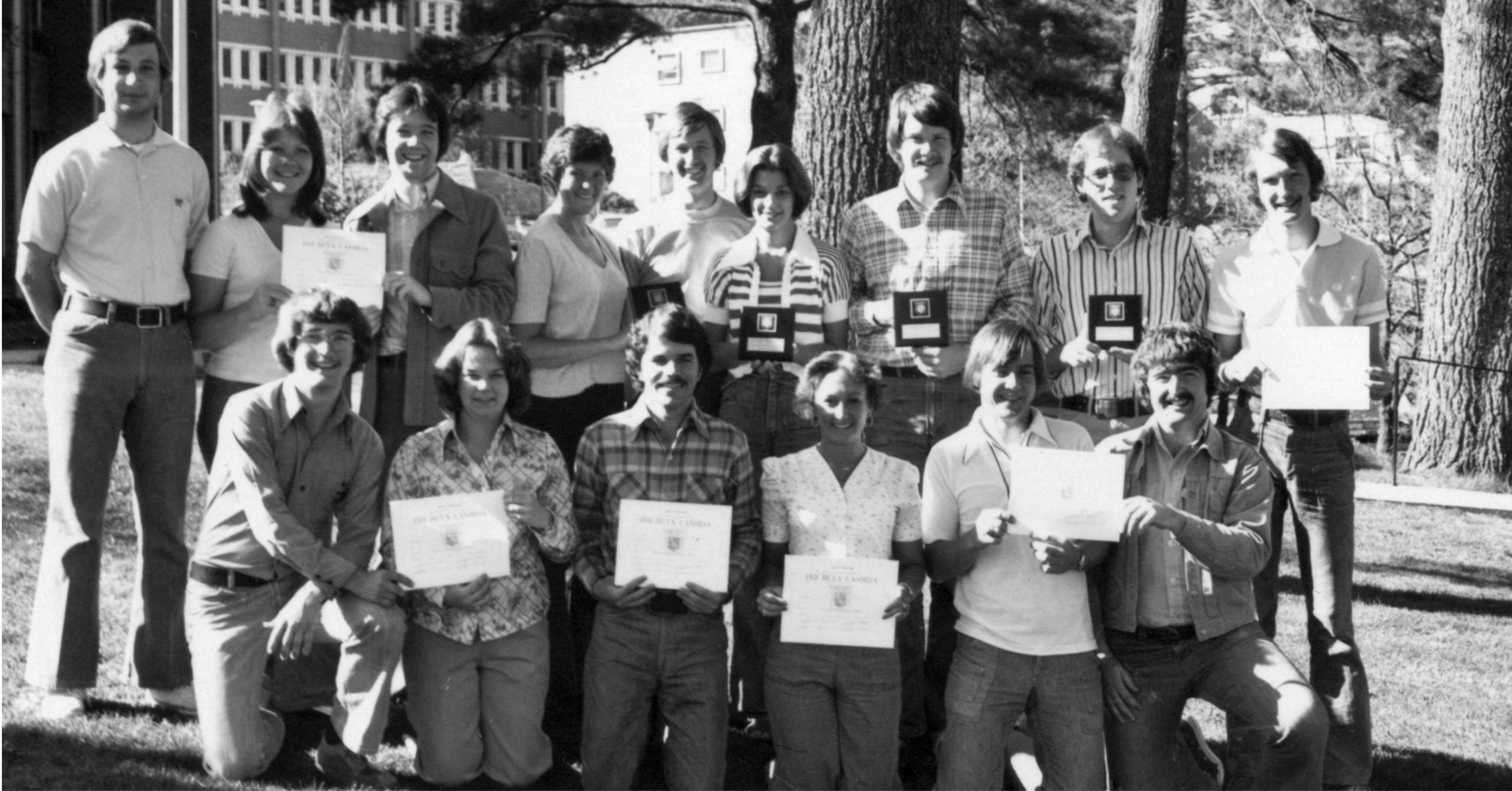 This image shows six members of the College of Business fraternity Phi Beta Lambda standing outside at Appalachian State University (1967-current) holding certificates and plaques in April 1976.