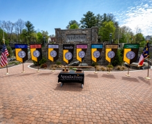 Displayed in front of the Appalachian State University sign, located in Founders Plaza on App State's campus, are the university mace and banner, along with the banners for App State's College of Arts and Sciences, Beaver College of Health Sciences, College of Fine and Applied Arts, Hayes School of Music, Reich College of Education, Walker College of Business and Cratis D. Williams School of Graduate Studies. The state flag is shown at far right and the U.S. flag is pictured at far left.
