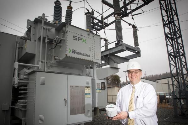 Data gathering: NRLP General Manager Ed Miller is holding an Advanced Metering Infrastructure (AMI) device which, when installed at the customer site, will enable measurement of detailed, time-based information and frequent collection and transmittal of such information to the supplier.