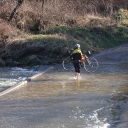 A cyclist crosses a flooded New River on foot, bike in hand.