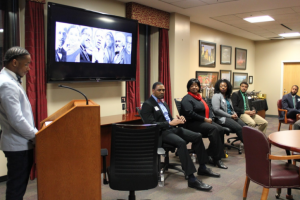 """Jonavan Adams, seated on the right, responds to a question posed by Jalen Sanders, left, the emcee of a panel discussion, """"Courageous Conversations.""""  The Walker College of Business collaborated early in February with Kappa Alpha Psi fraternity to hold a panel discussion, in observance of Black History Month. Seated beside Adams are fellow panelists Ramona Harris,'16, Kacey Griffin 13, and current MBA student, Patrick Preudhomme."""